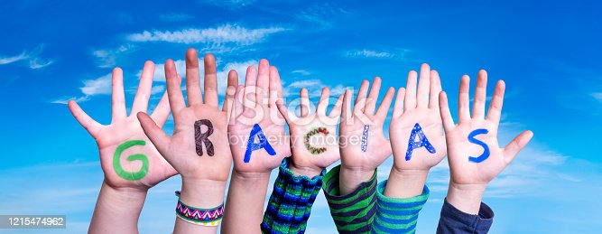 516544386 istock photo Many Children Hands Building Word Gracias Means Thank You, Blue Sky 1215474962