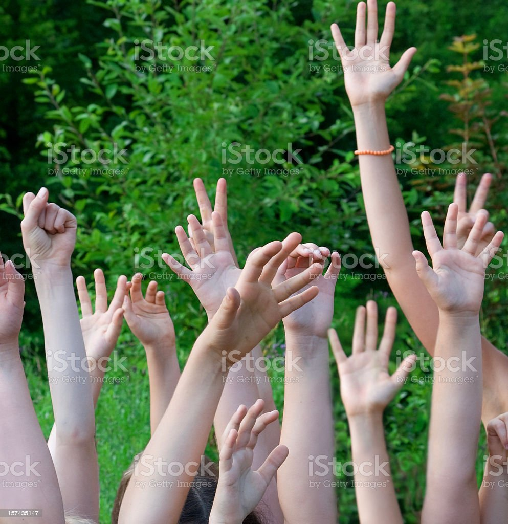 many children hands in the air want more atention stock photo