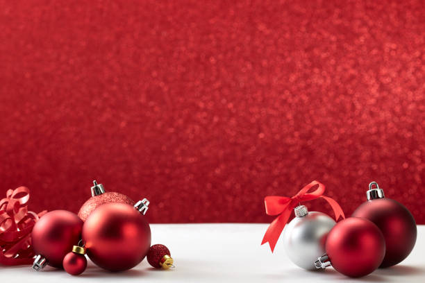 Cтоковое фото many christmas balls on white table red wall