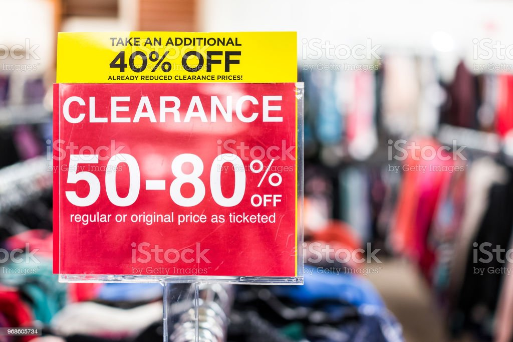 Muitas roupas bokeh em loja de disconto, vestuário pendurado na prateleiras cabides linha closeup com sinal de despejo vermelho grande, preços reduzidos - foto de acervo