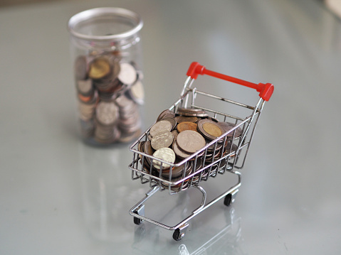 1155852718 istock photo Many, coins, clear plastic, cans, mini, model, cart, supermarket, out of focus background,blur, cash, money, coin, bank, investment, banking, currency, financial, savings, background, wealth, profit, economy, rich, growth, commerce, gold, tax, business, s 1264242659