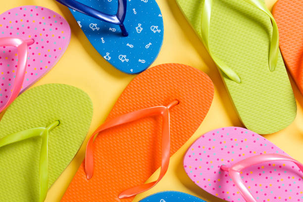 many colored flip flops on yellow background. Copy space top view stock photo
