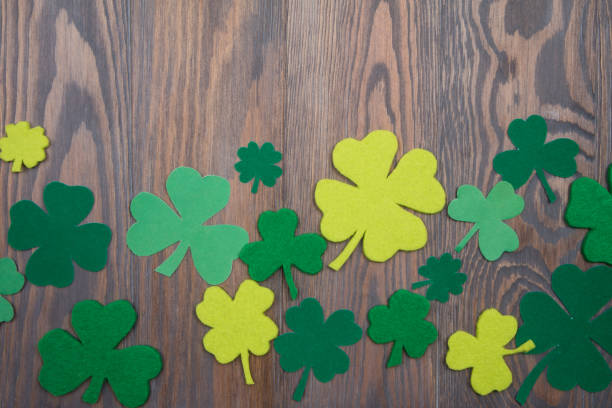 many colored green clover leaves on wooden background. patricks day - happy st. patricks day stock photos and pictures