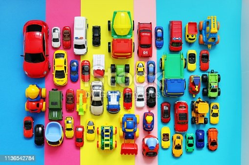 Many colored toy cars on multicolored background, top view