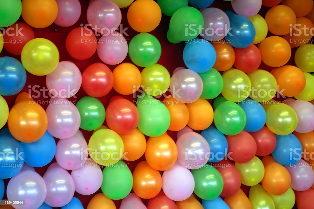 Many colorful balloons attached to a red wall stock photo