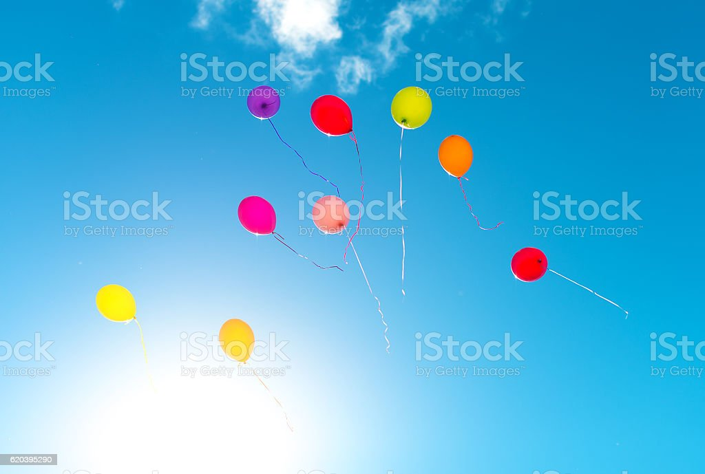 Many colorful baloons in the blue sky. stock photo