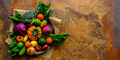 Many colorful contrast color salad vegetables and lemon and lime, sitting in a round, old, wooden vegetable bowl on burlap sack material on an abstract terracotta rustic background with atmospheric lighting, with good copy space to the right of the image.
