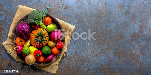 istock Many colorful contrast color salad vegetables and lemon and lime, sitting in a round, old, wooden vegetable bowl on burlap sack material on an abstract blue/grey rustic background with atmospheric lighting. 1088349716