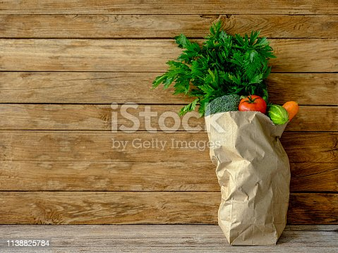istock Many colorful contrast color salad vegetables in a brown paper supermarket shopping bag on an old wooden table against an old weathered wood panel background wall. 1138825784
