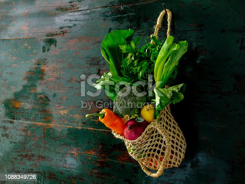 istock Many colorful contrast color salad vegetables in a reusable string jute bag hanging from an old weathered wood abstract color contrasting turquoise colored background wall. 1088349726