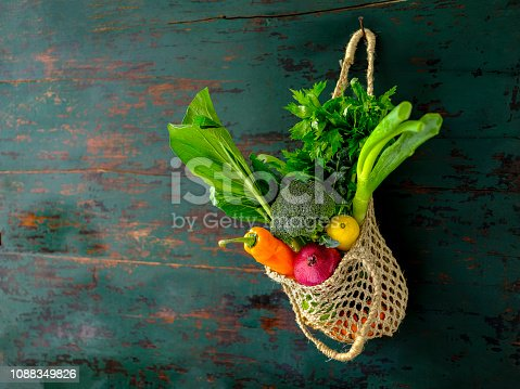 istock Many colorful contrast color salad vegetables in a reusable string jute bag hanging from an old weathered wood abstract color contrasting turquoise colored background wall. 1088349826