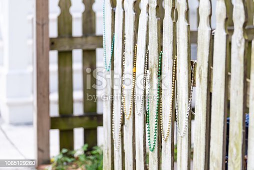 889246424istockphoto Many colorful mardi gras festival necklace beads, with green yellow colors, hanging on wooden fence in downtown historic New Orleans city in Louisiana, USA 1065129260