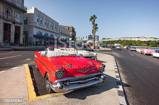 November 27, 2019, Havana, Cuba: Many colorful taxis are parked on the Malecon promenade in the center of old Havana against the background el Morro lighhouse