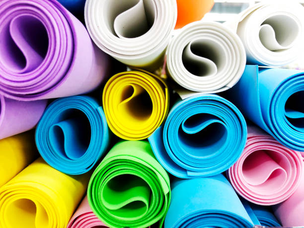 Many colorful yoga mats as background. Rolled yoga exercise mats against white stock photo