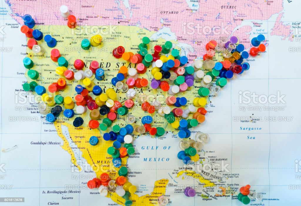 Many colourful pins in a wall map of America showing origin of visiting tourists stock photo