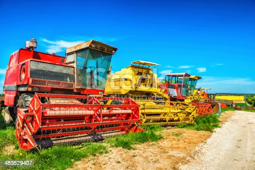 istock Many Combines Harvester on The Field 483529407