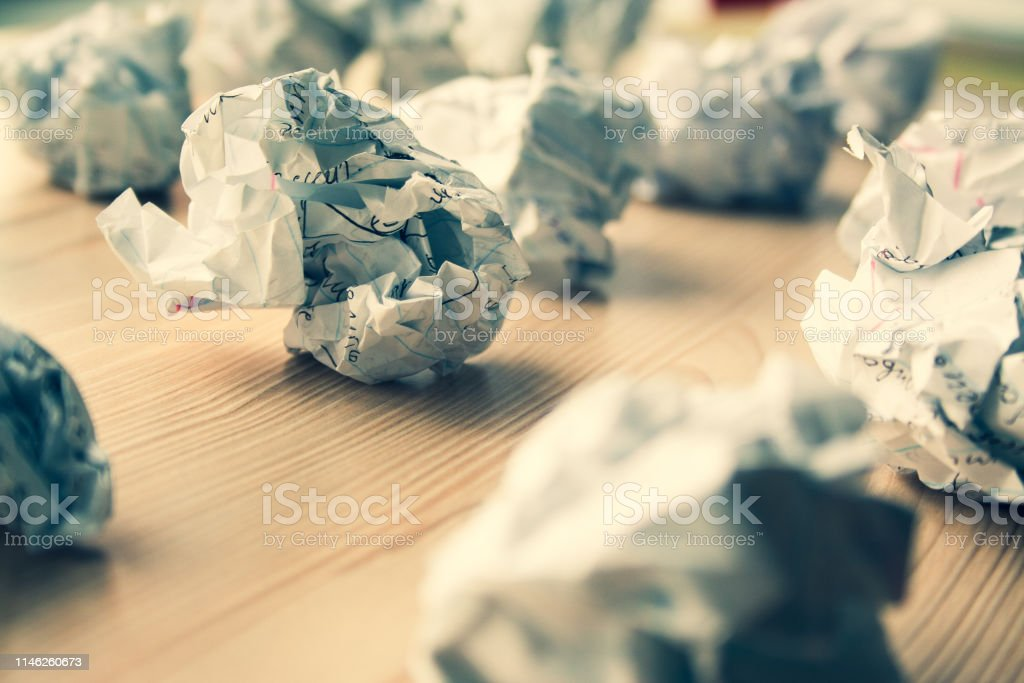 Many crumpled white paper balls on wooden table. Texture of crumpled...