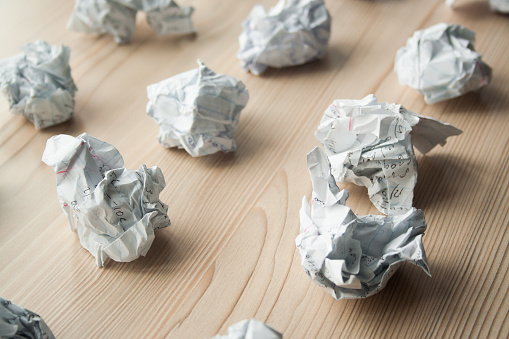 istock Many crumpled white paper balls on wooden table. Texture of crumpled paper balls.  Crumpled paper as brainstorming, creativity concept, mistakes and creation symbol. 1146260686