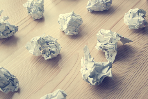 istock Many crumpled white paper balls on wooden table. Texture of crumpled paper balls.  Crumpled paper as brainstorming, creativity concept, mistakes and creation symbol. toned 1146260689