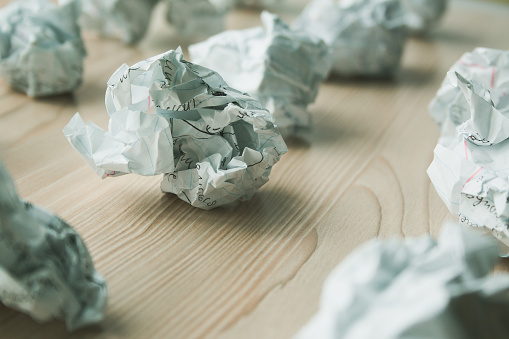 istock Many crumpled white paper balls on wooden table. Texture of crumpled paper balls.  Crumpled paper as brainstorming, creativity concept, mistakes and creation symbol. 1146260734