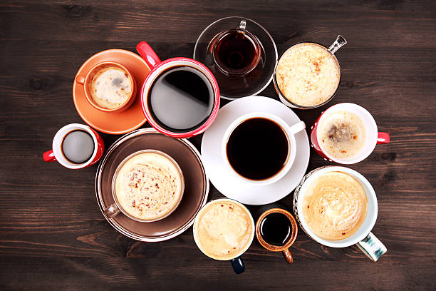 Many cups of coffee on wooden table Many different cups of coffee on dark wooden table, top view. caffeine stock pictures, royalty-free photos & images