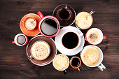 Many cups of coffee on wooden table