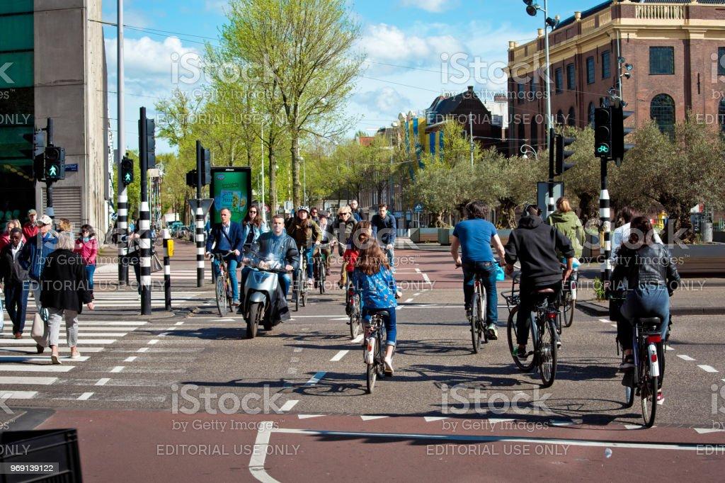 Muchos ciclistas en la calle de Amsterdam en países bajos - Foto de stock de Adulto libre de derechos