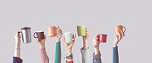 Many different arms raised up holding coffee cup