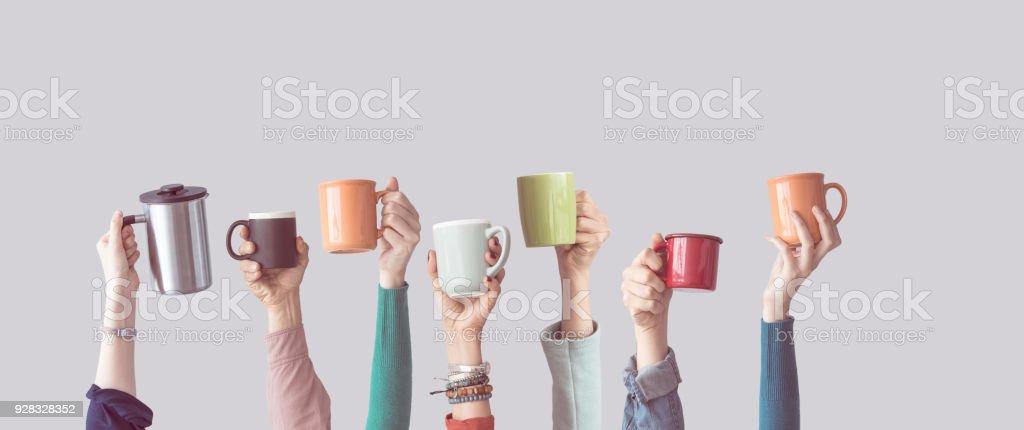 Viele verschiedene Arme angehoben halten Kaffeetasse – Foto