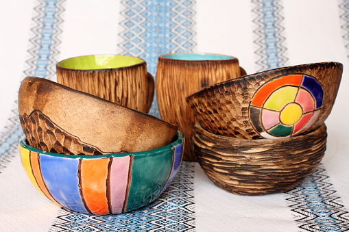 Many different bright multicolored ceramic handcrafted bowls and cups. Ceramics in the interior