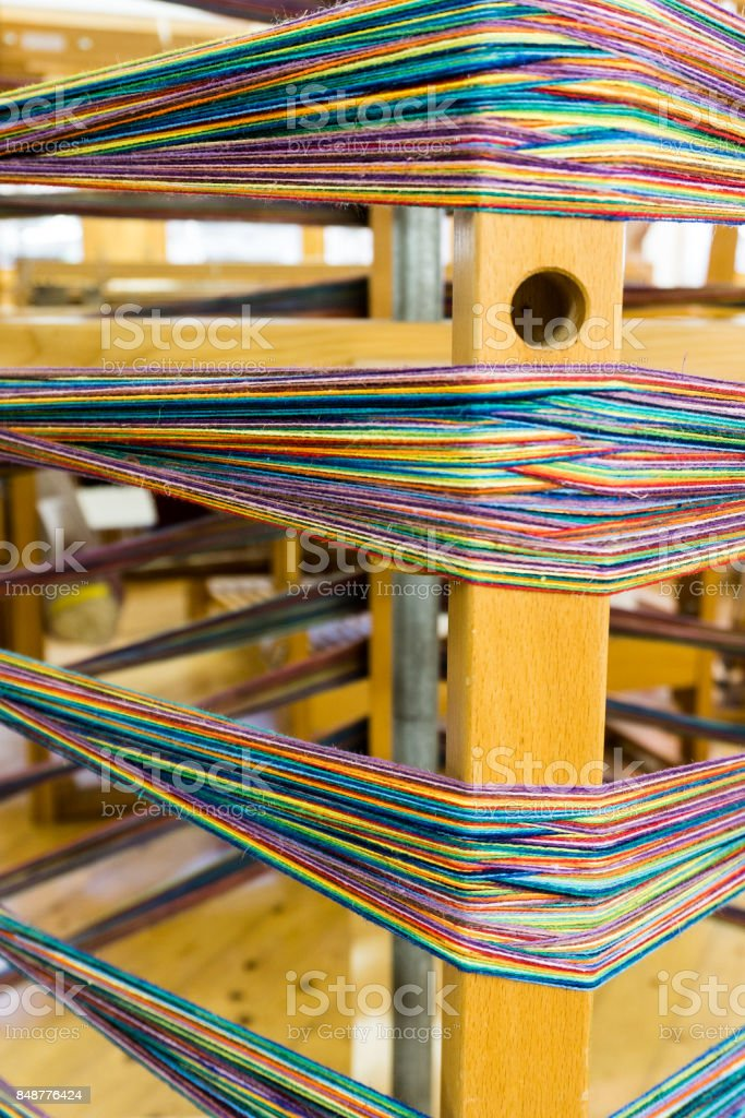 many different color thrreads ready for spools and weaving on traditional looms stock photo