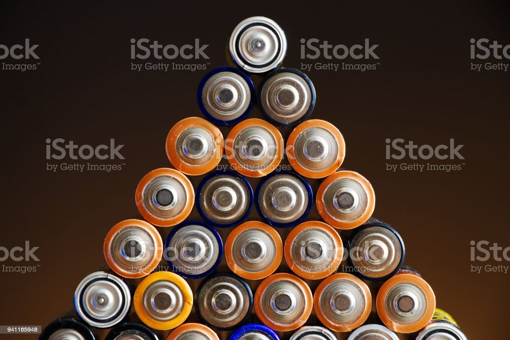 Many different colored AA batteries arranged in a pyramid on a dark gradient background stock photo
