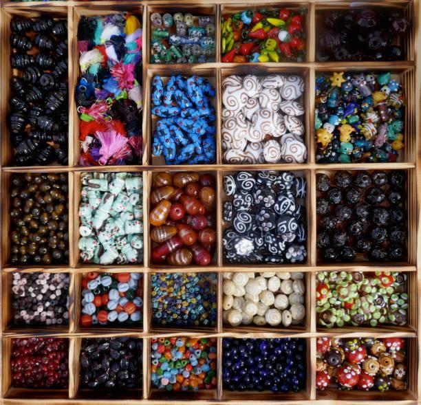 viele verschiedene, bunte glasperlen, sortiert in einer holzkiste. - bastelshop stock-fotos und bilder
