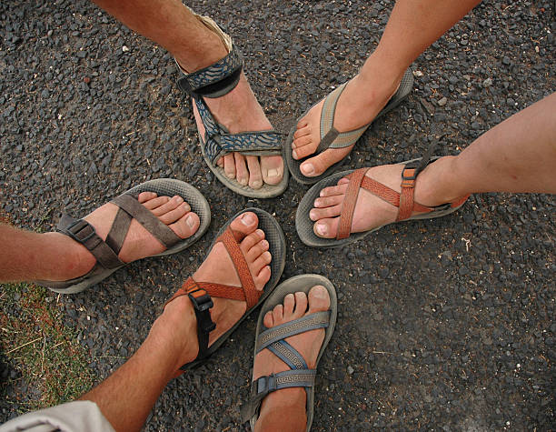 Many different feet and sandals form a circle stock photo