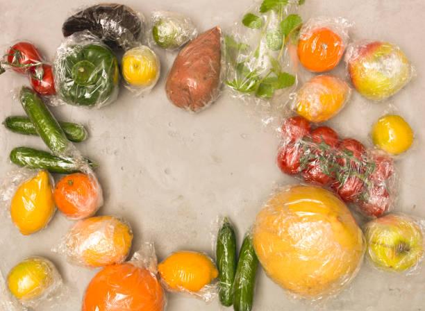 viele verschiedene Früchte und Gemüse werden in Plastikfolie verpackt auf konkrete Hintergrund verpackt. – Foto