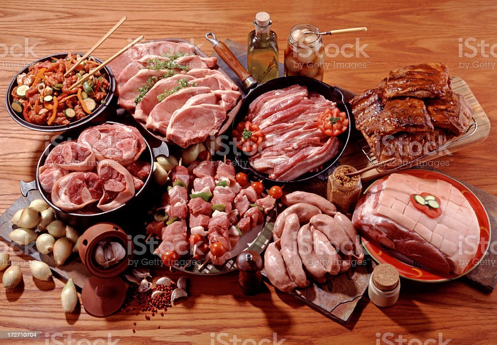 Many different raw pork cuts on a wooden counter royalty-free stock photo