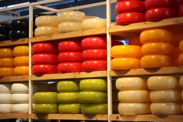 viele verschiedene formen von farbigem holländischem käse, der auf gepflegten regalen gestapelt ist. kulinarisches produkt typisch für amsterdam - günstig nach amsterdam stock-fotos und bilder