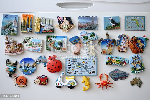 Many different souvenir magnets on the fridge