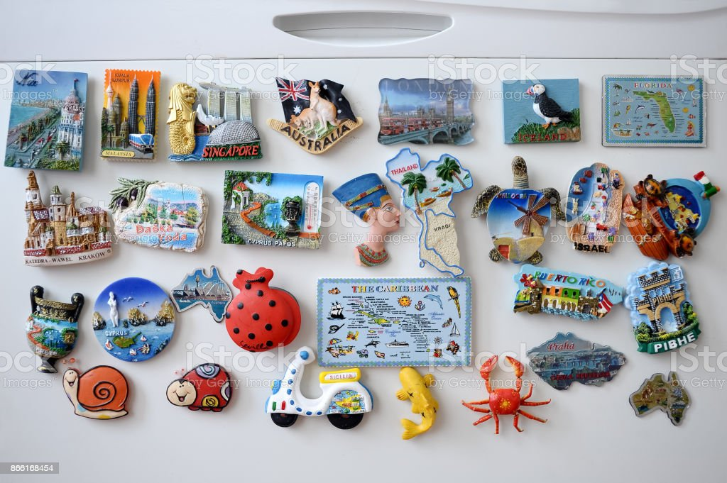 Many different souvenir magnets on the fridge stock photo