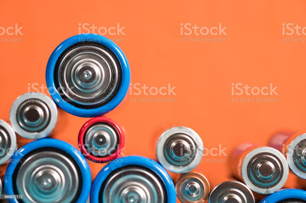 Many different types used or new battery, rechargeable accumulator, alkaline batteries on color background. Nature energy stock photo