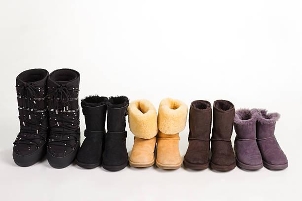 many different winter boots on a white background. - lammfellstiefel stock-fotos und bilder