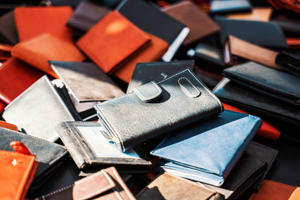 Many differently colored purses stacked on a marketplace on a sunny day stock photo