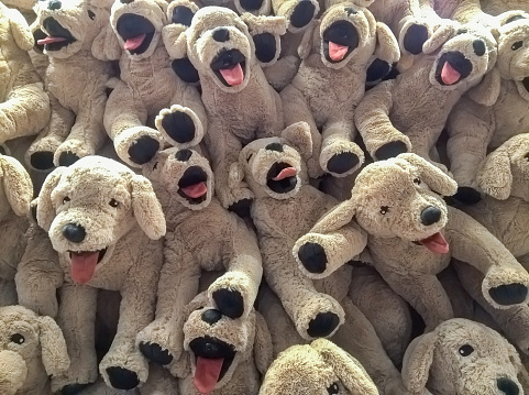 many dog dolls hang on the wall for sale in store.