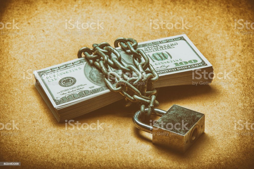 many dollars is locked with chain, vintage color. many dollars is locked with chain, vintage color. Bank - Financial Building Stock Photo
