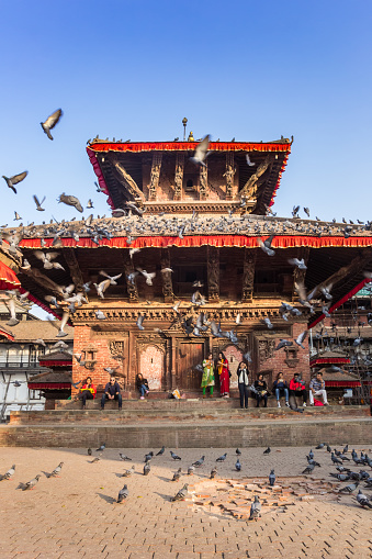 Many doves flying up at the Durbar square in Kathmandu, Nepal