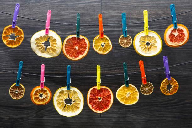 viele getrocknete stücke von verschiedenen zitrusfrüchten hängen farbige wäscheklammern - orangenscheiben trocknen stock-fotos und bilder
