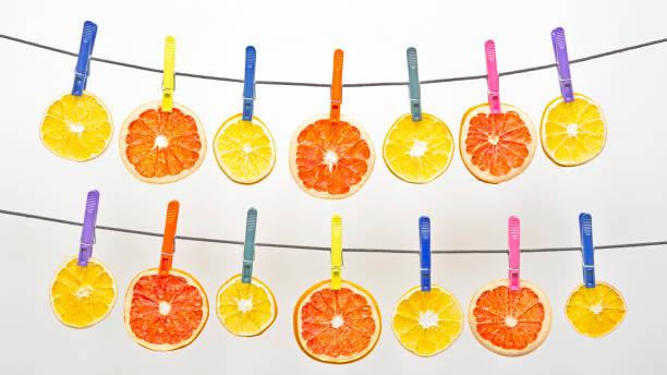 viele getrocknete stücke von verschiedenen zitrusfrüchten hängen an farbigen wäscheklammern - orangenscheiben trocknen stock-fotos und bilder