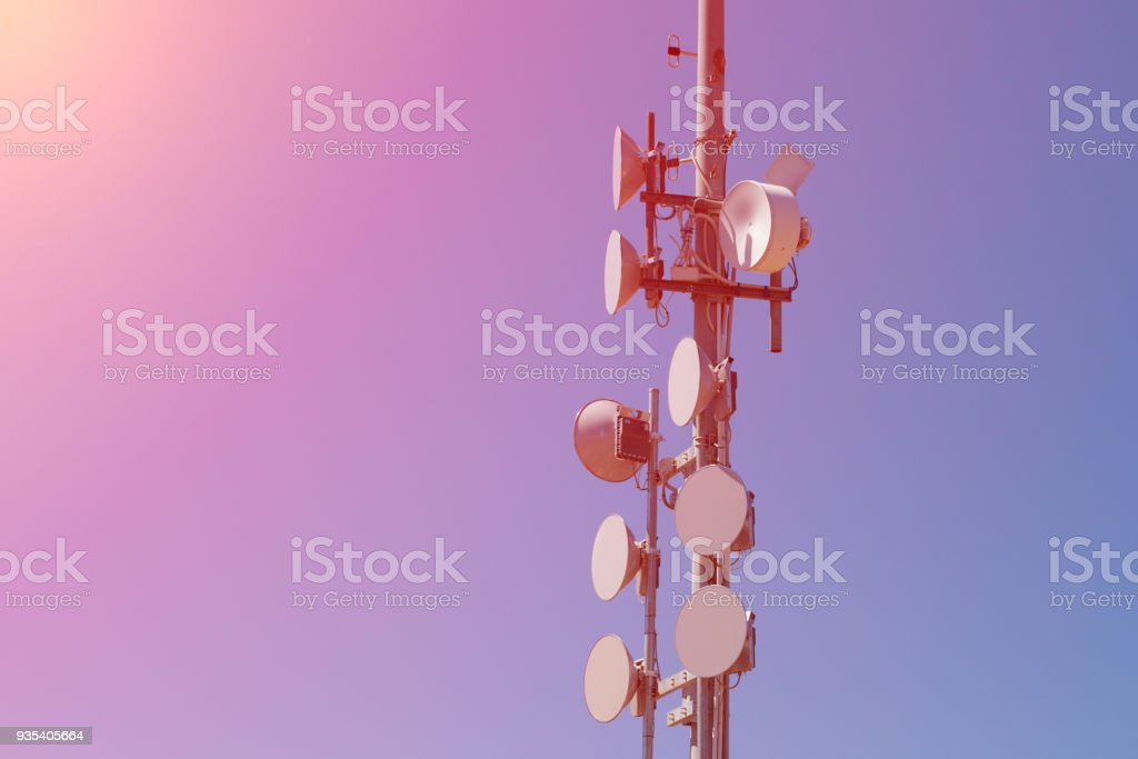 Many drum antennas on a pole at sunset with blue sky as background stock photo