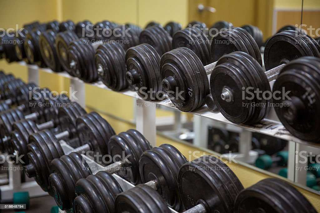 many dumbbells in gym stock photo