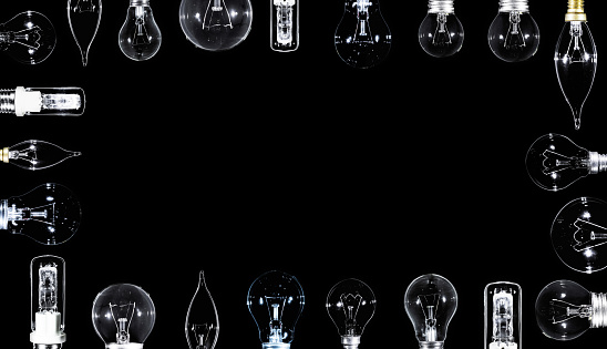Many Edison lamps over black background, copyspace frame